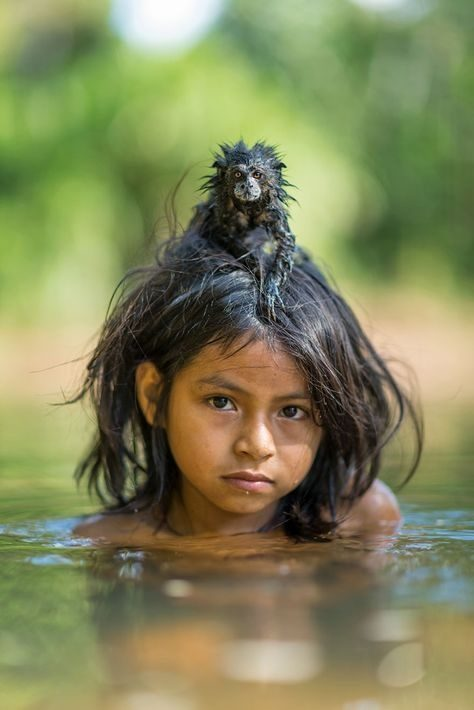 Opica z otrokom plava v reki